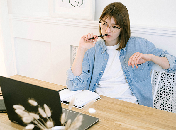 Woman thinking in front of laptop